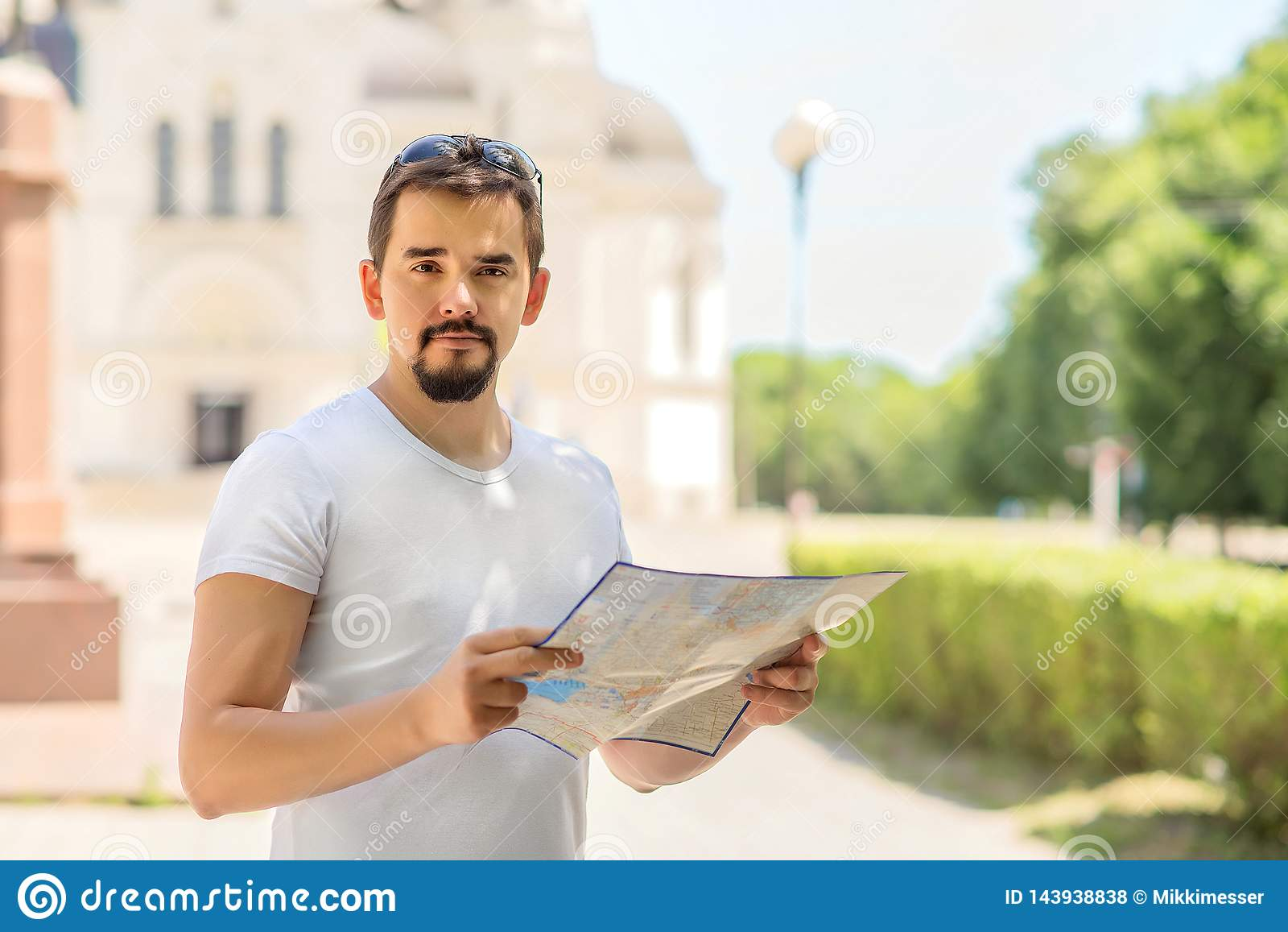 Travel and vacation concept: attractive adult male tourist with a paper map on city square or street in sunny day. Copy space