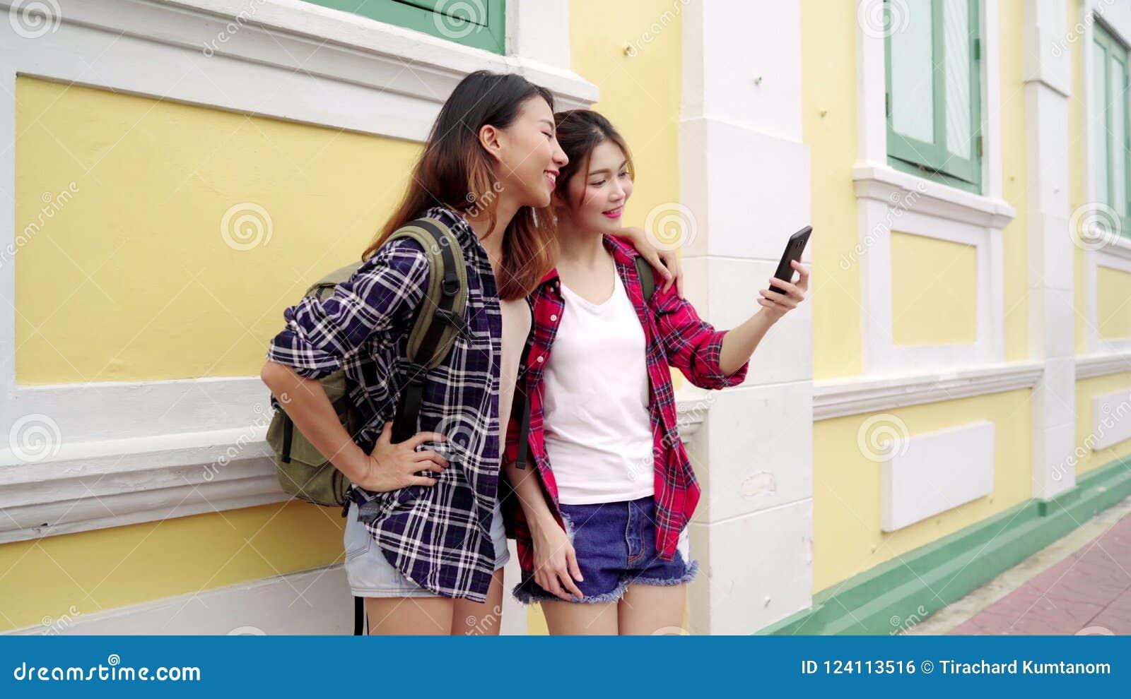 Traveler backpacker Asian women lesbian lgbt couple travel in Bangkok,  Thailand. Happy blogger young female couple using smartphon.