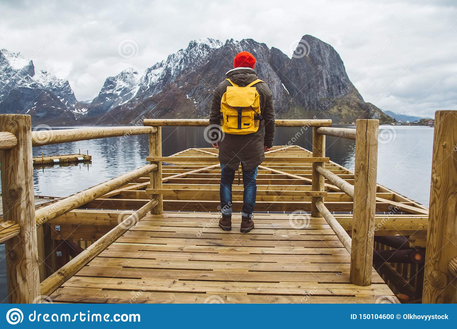 Traveler man with a yellow backpack wearing a red hat standing on the background of mountain and lake wooden pier