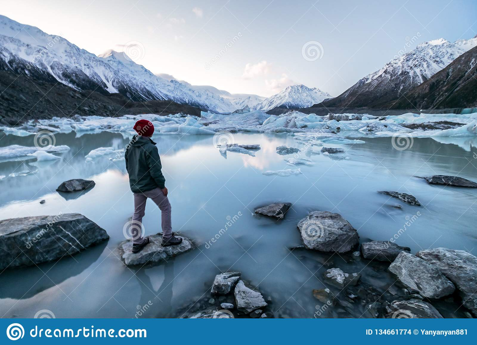 A traveler viewing the amazing icebergs and snow mountains in Tasman Valley, New Zealand