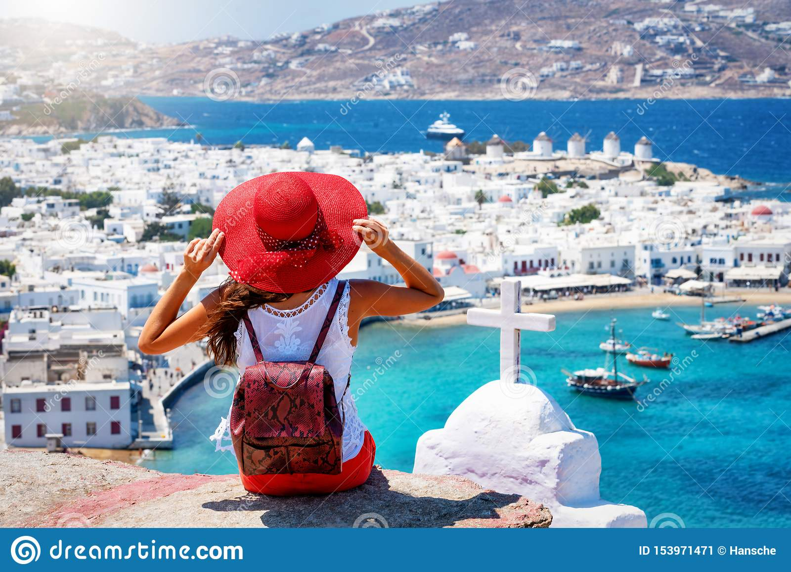 Traveler woman enjoys the view over the town of Mykonos island, Cyclades, Greece