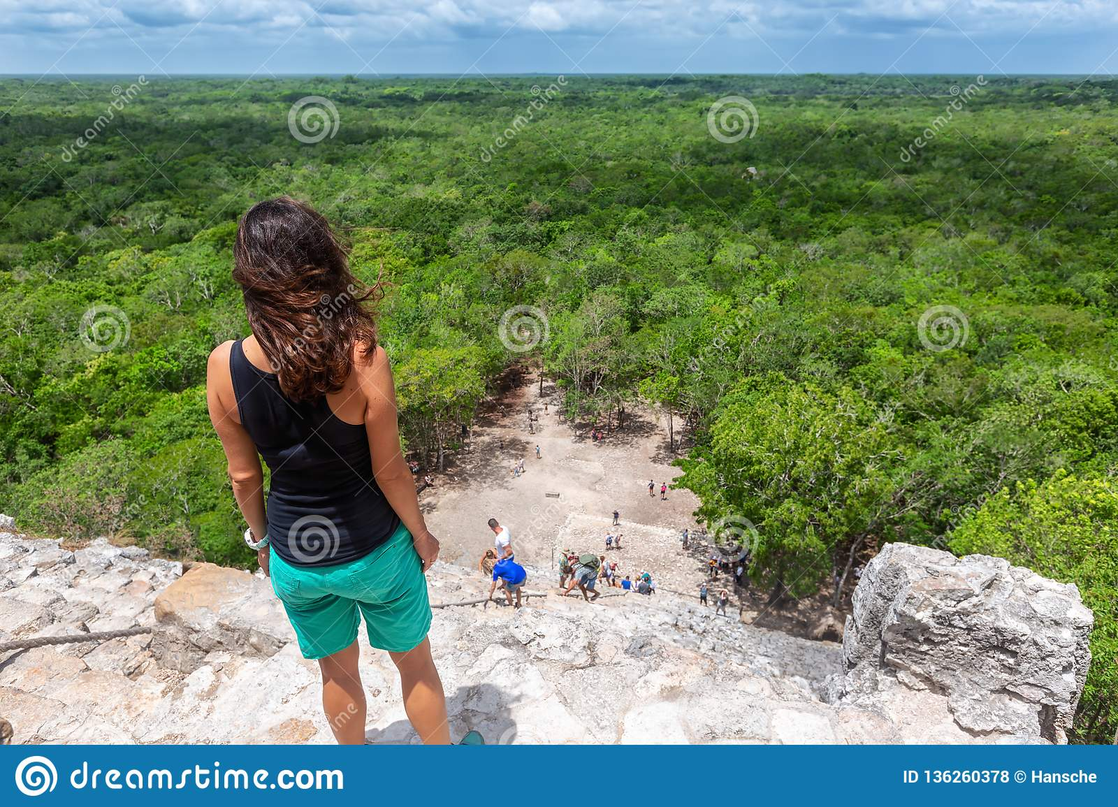 Traveler woman looks the Nohoch Mul pyramid in Coba, Yucatan, Mexico