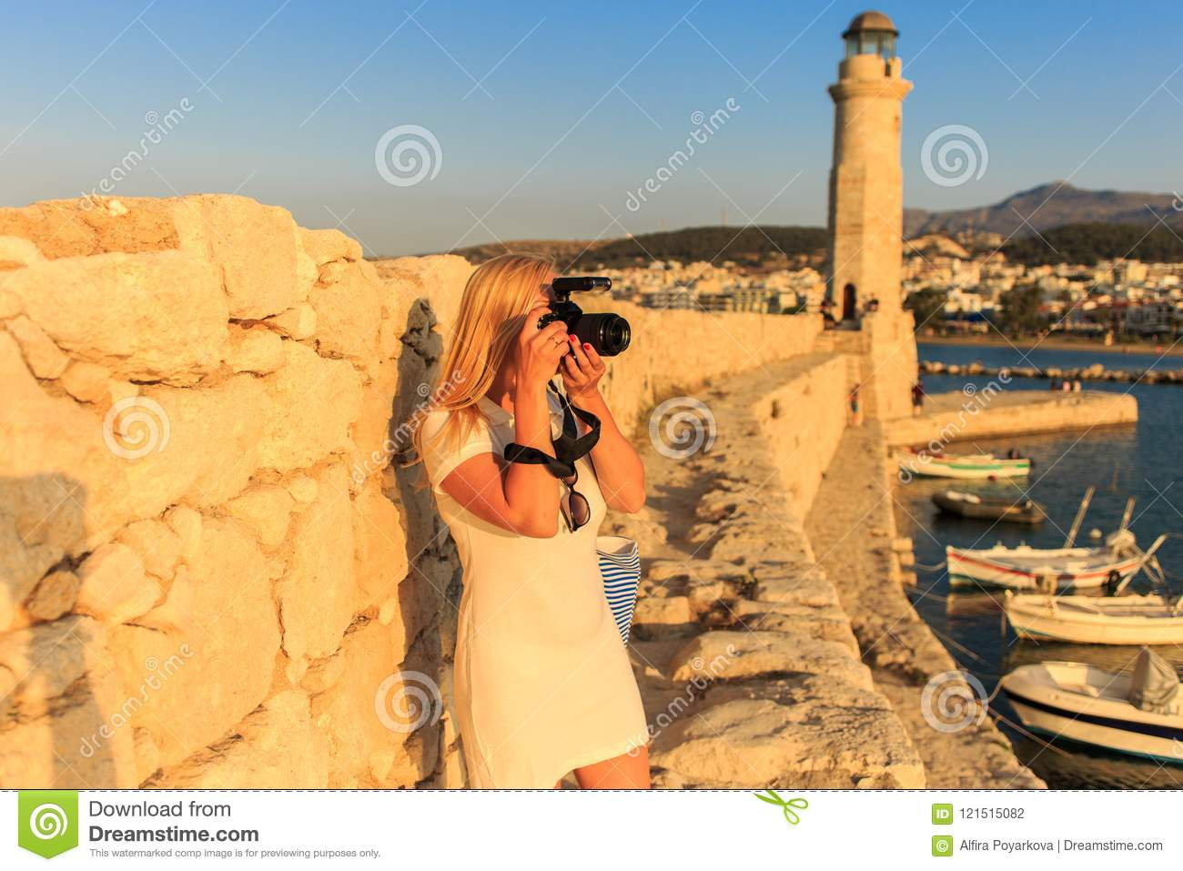 Traveler woman photographer with professional camera takes shot of Rethymno,Crete, Greece.
