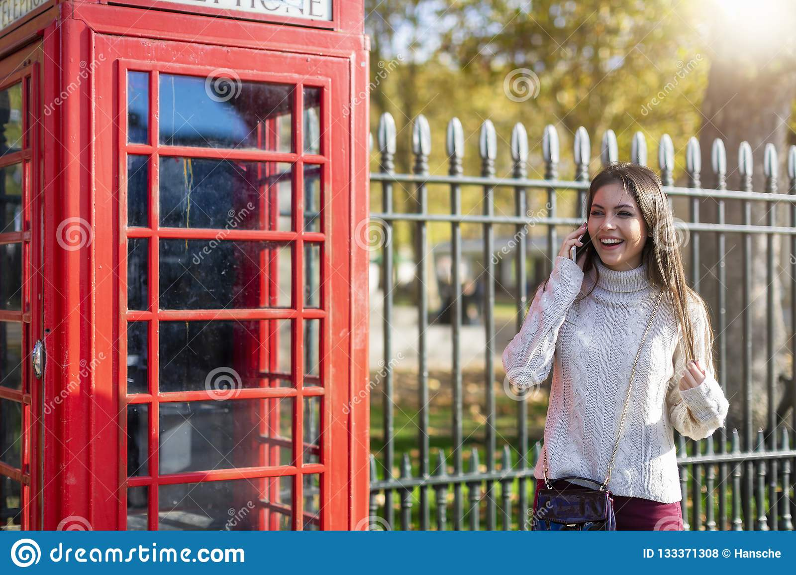 Traveler woman talks on her cellphone next to a red telephone booth in London, UK