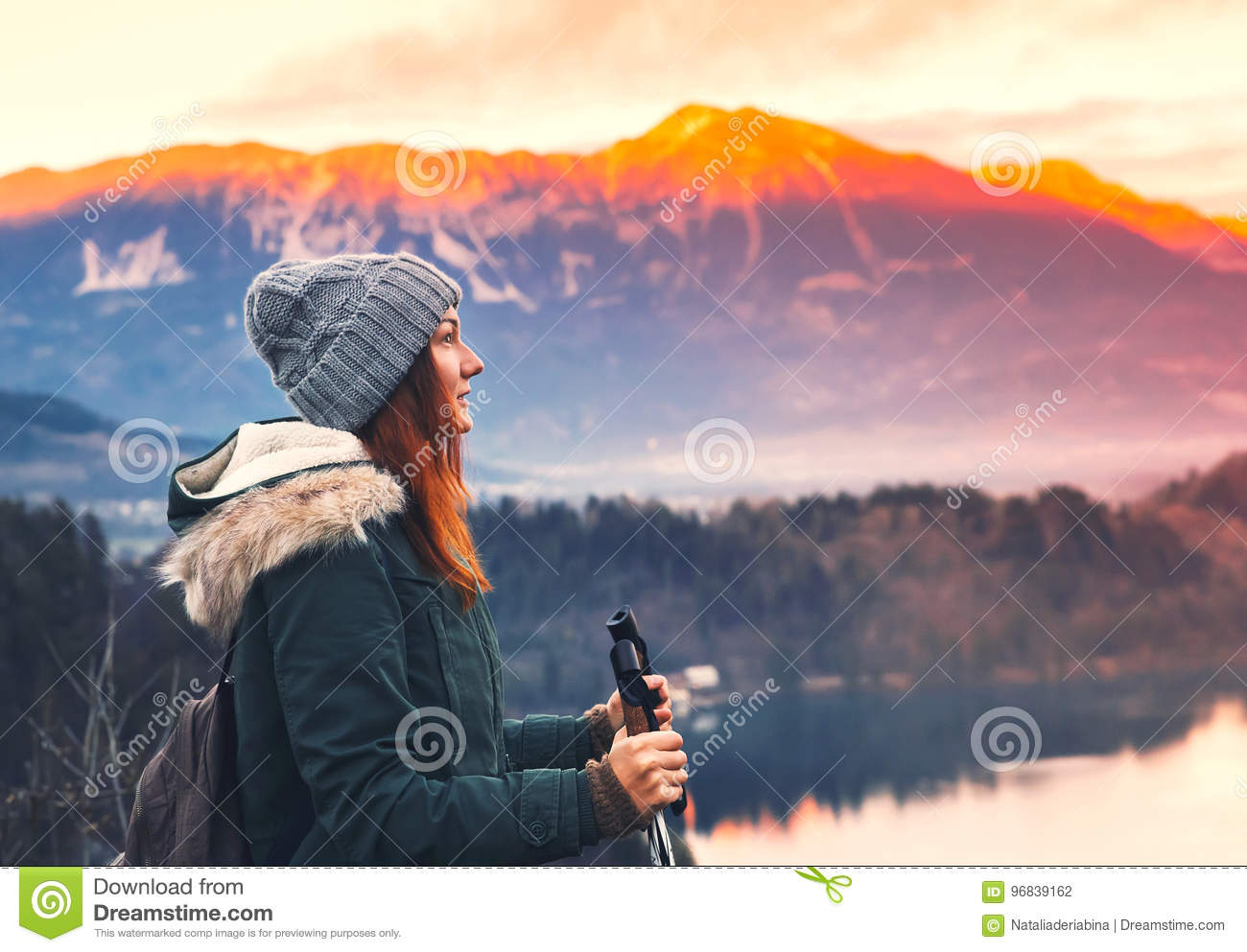 Traveling young woman looking on sunset on Bled Lake, Slovenia,