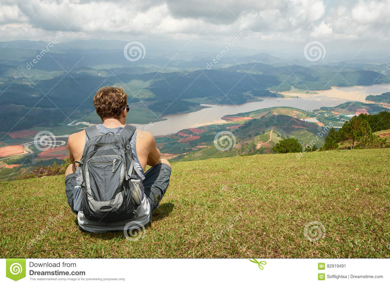 Traveller gray backpack resting enjoying the sunny valley of mountains in the background