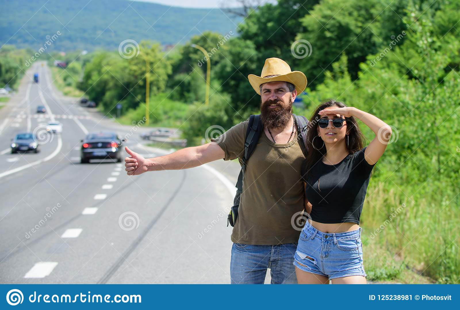 Travellers try to stop car. Hitchhiking is one of cheapest ways of traveling. Couple hitchhikers travelling summer sunny