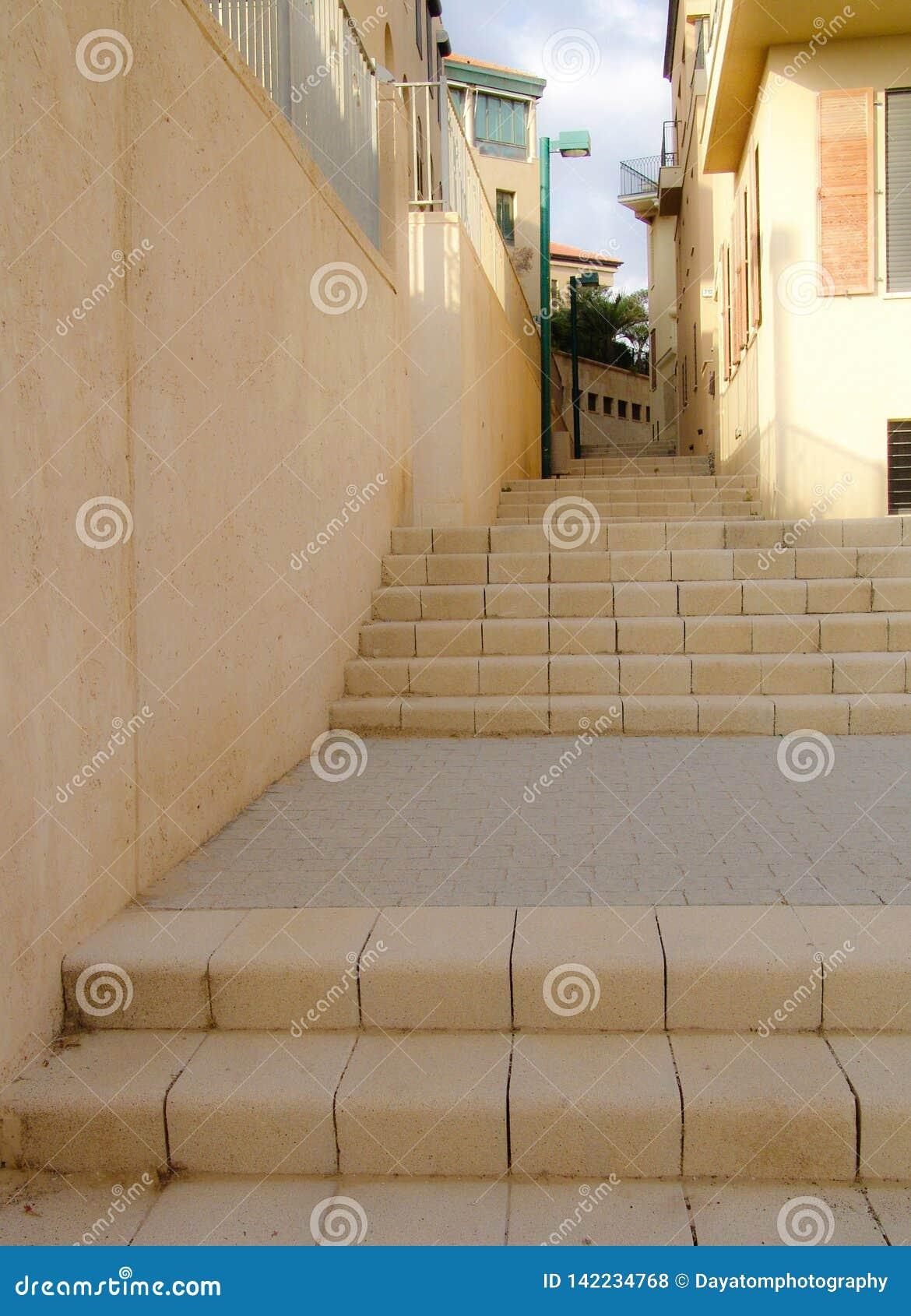 Trayectoria amarilla de las escaleras de la ciudad que mira para arriba entre una pared y edificios residenciales, mostrando un p