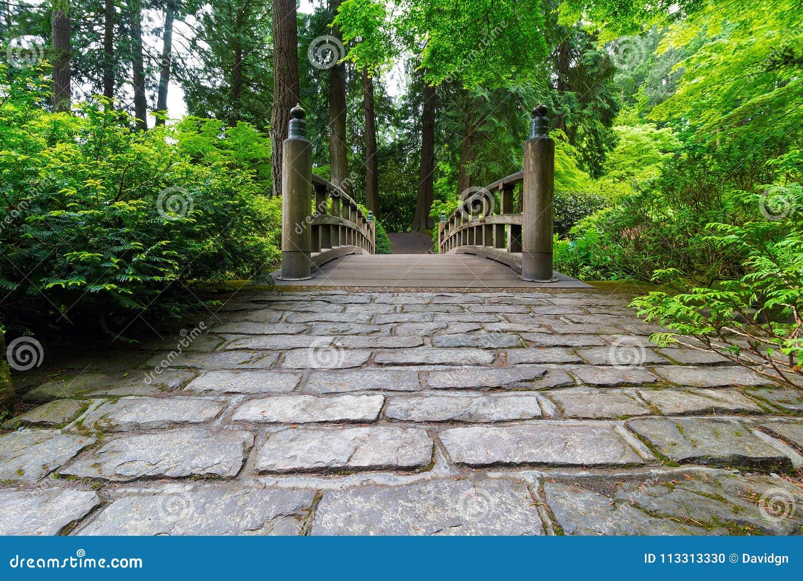 Trayectoria del guijarro al puente de madera en jardín japonés manicured