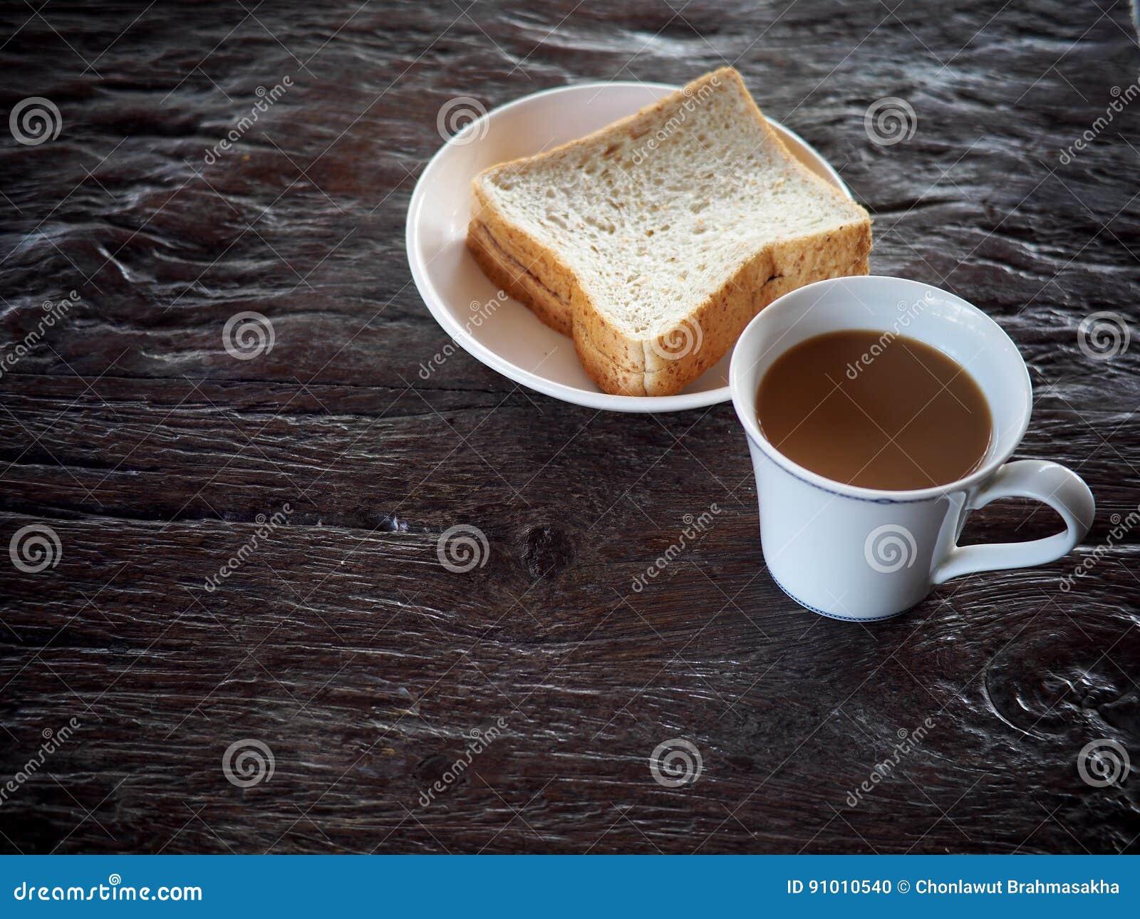 Trayez le café en feuilles blanches de pain de tasse et de blé entier de porcelaine