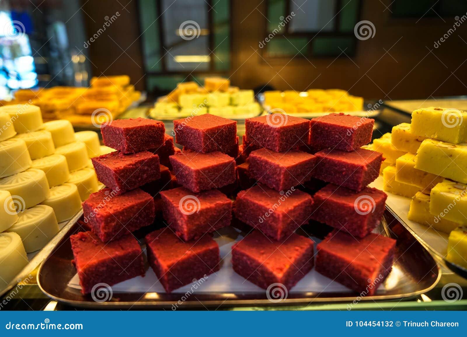 Trays full of stack colorful red velvet Indian sweet dessert in bakery showcase