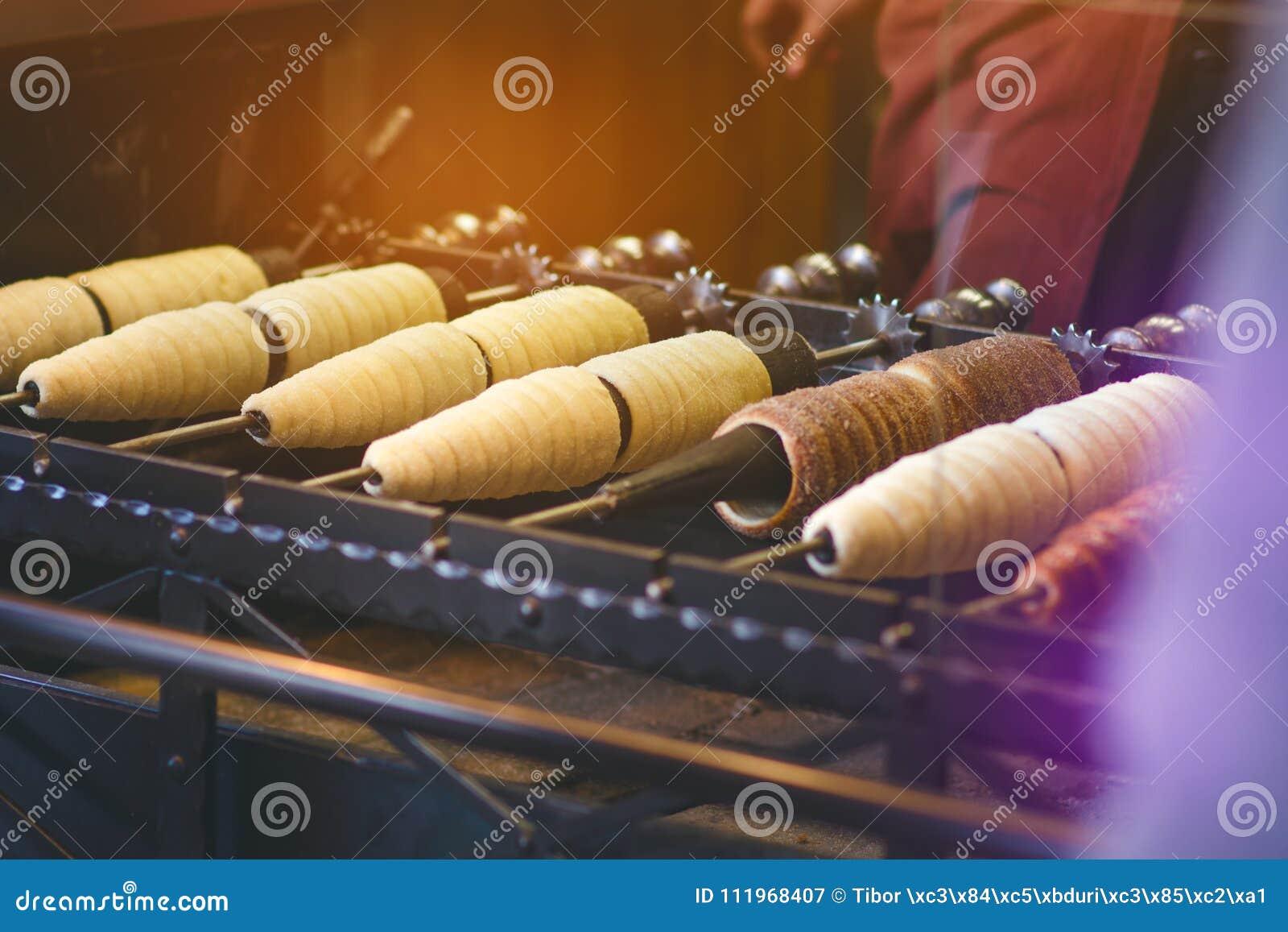Trdelnik eller trdloen är den traditionella tjeckiska sötsaken Trdlo för kvinnahanduppehälle i den Prague gatan Gatamat