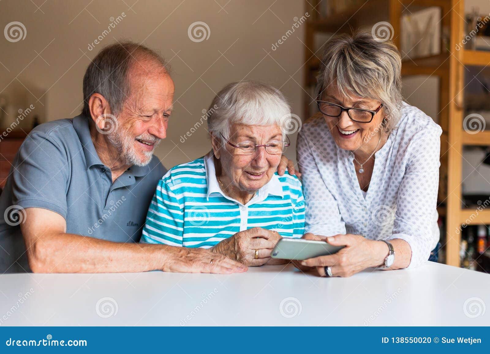 Tre äldre personer som använder den smarta telefonen