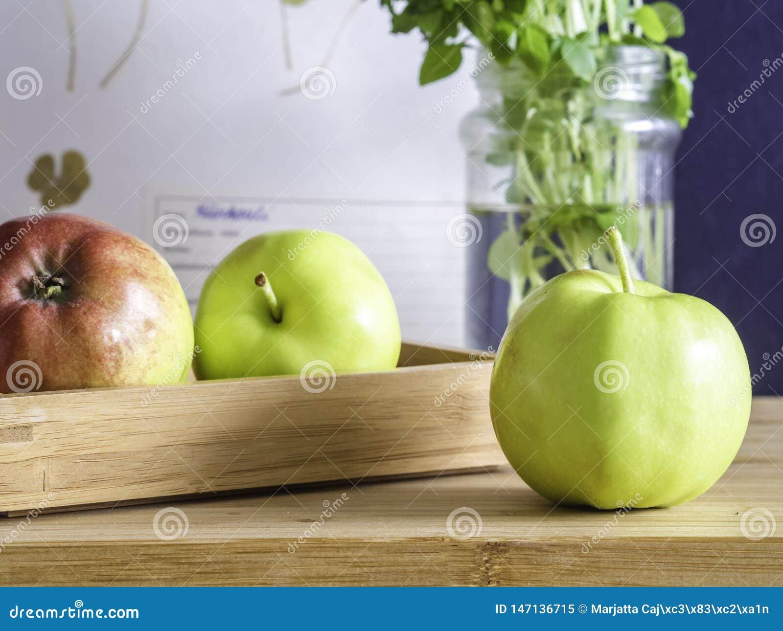 Tre äpplen på en tabell med en träask