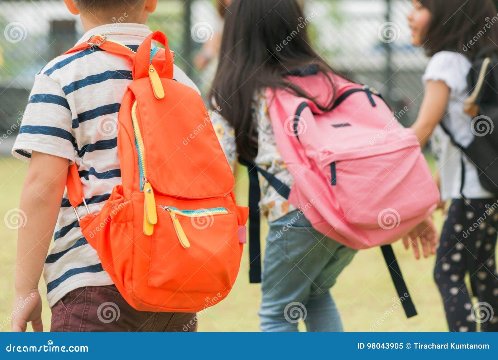 Tre allievi della scuola primaria vanno di pari passo Ragazzo e ragazza con le borse di scuola dietro la parte posteriore Inizio