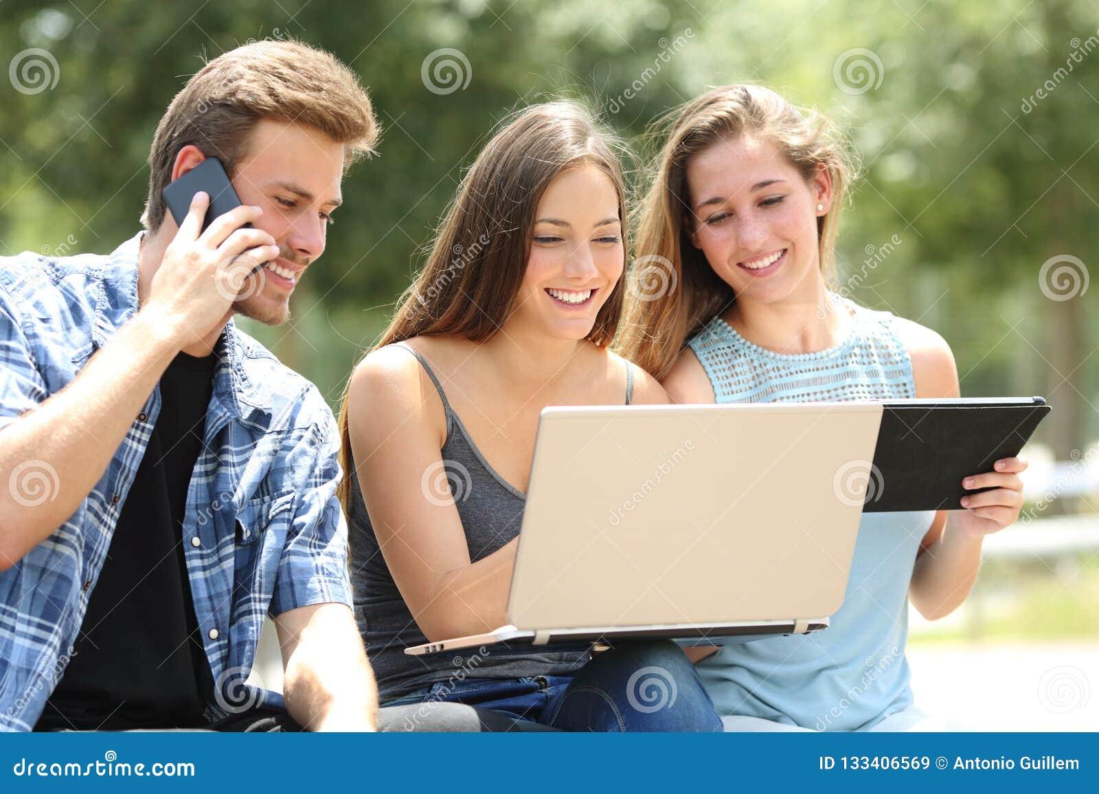 Tre amici che utilizzano i dispositivi multipli in un parco