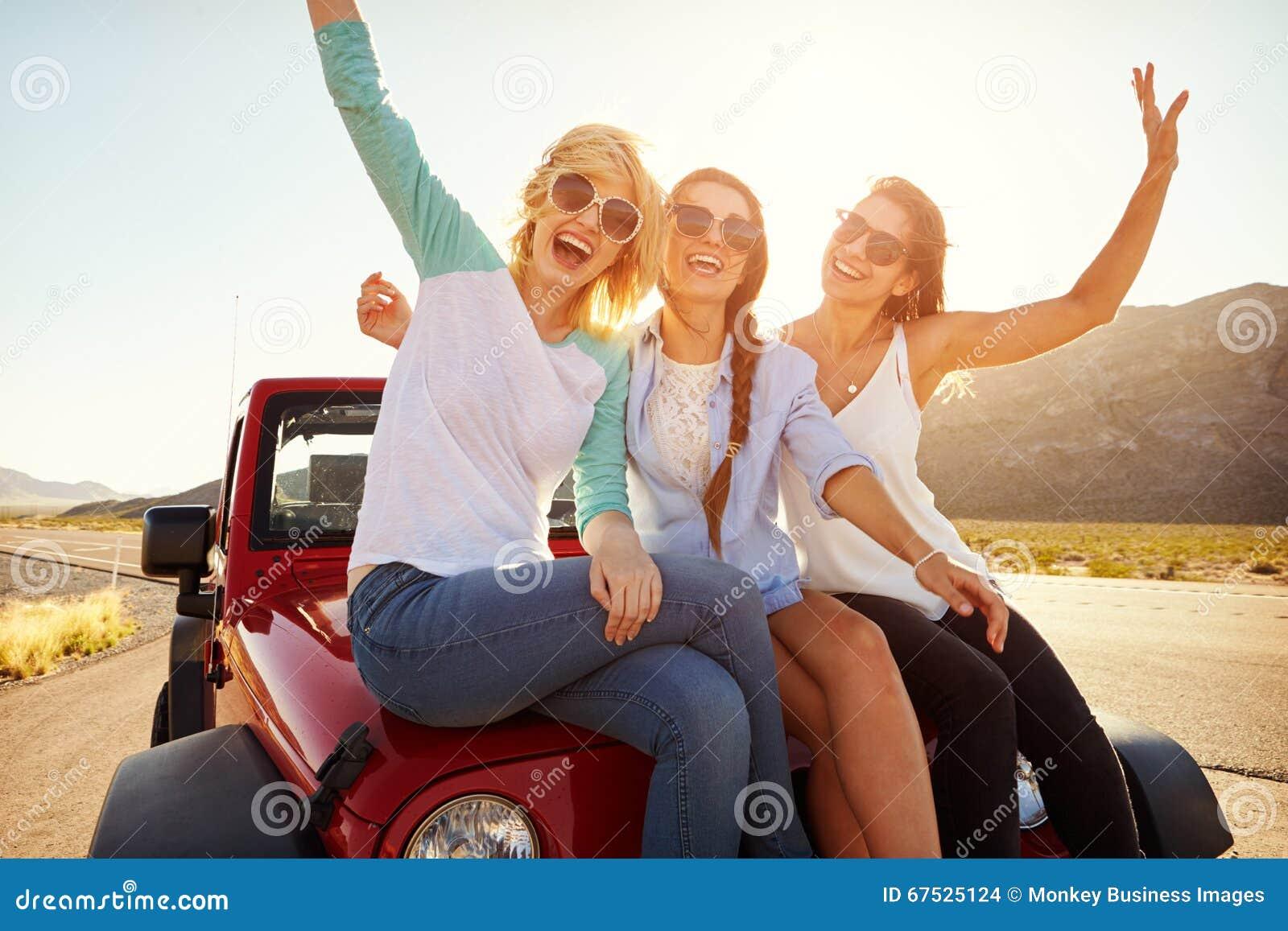Tre amici femminili sul viaggio stradale Sit On Car Hood