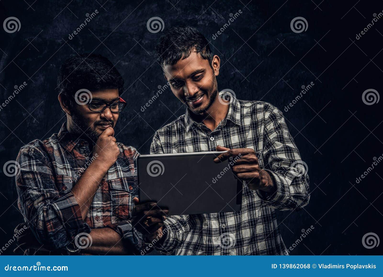 Tre amici indiani felici in abbigliamento casual stanno in un abbraccio e selfie di presa sullo smartphone