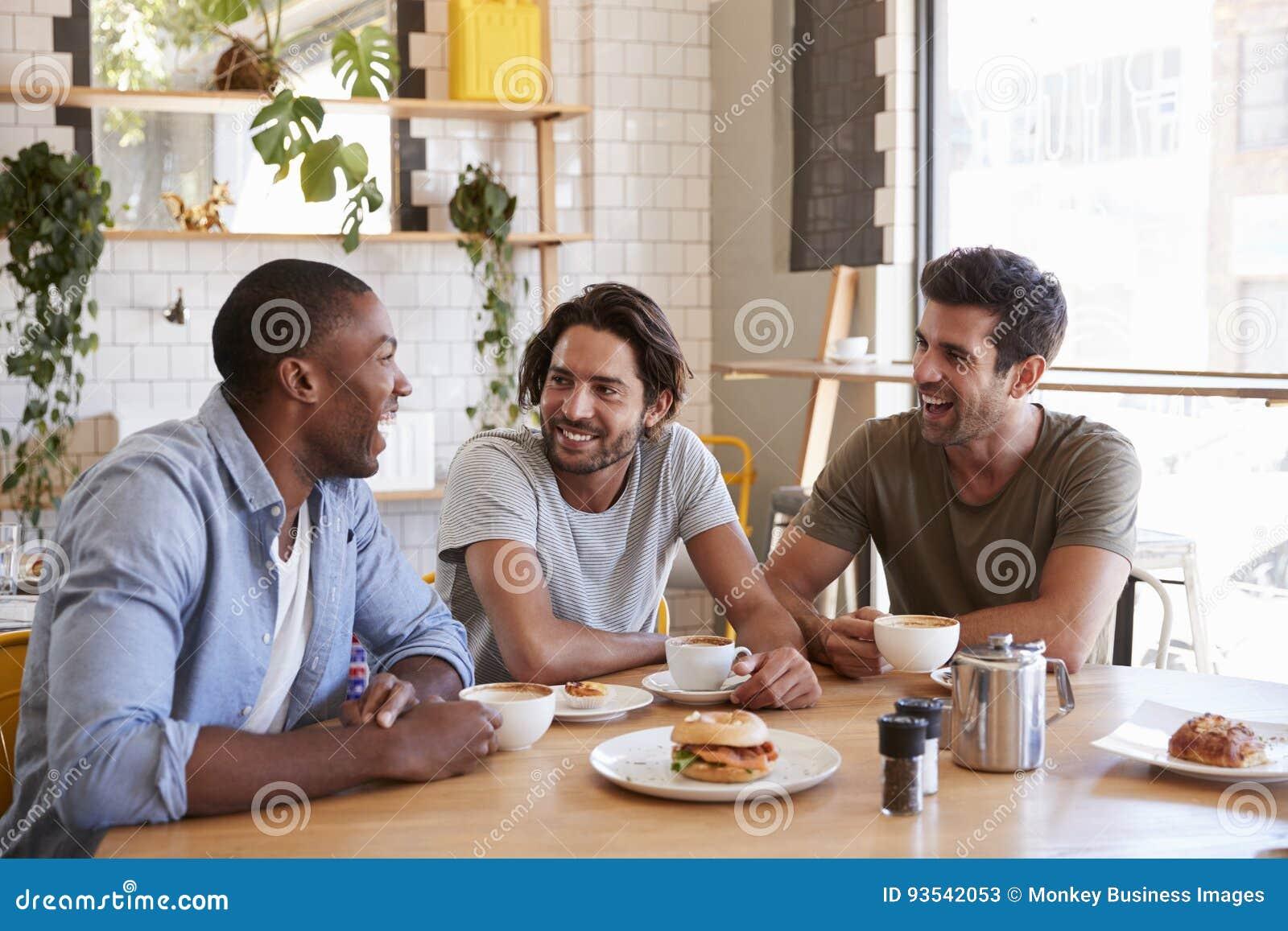 Tre amici maschii che si incontrano per il pranzo in caffetteria