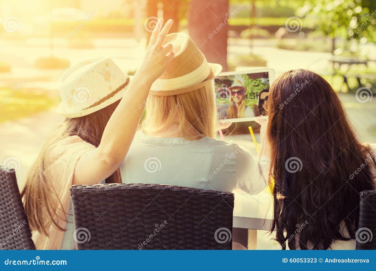 Tre attraktiva hipsterflickor som tar en selfie med den digitala minnestavlan