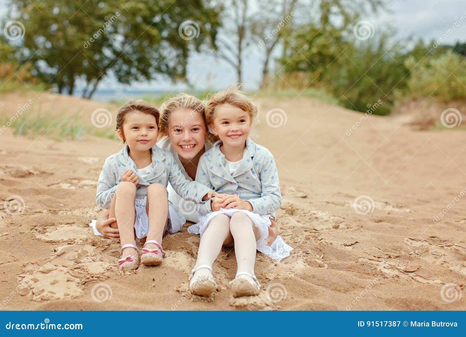 Tre bambine sono sorelle adorabili che abbracciano sul backgroun