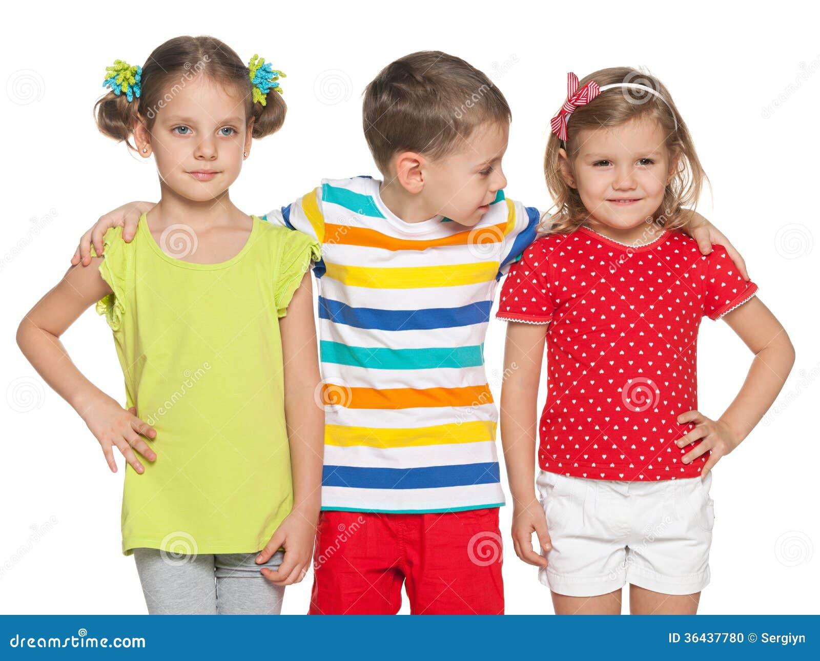 5783e372866b Tre bambini con differenti emozioni stanno stando insieme sui precedenti  bianchi