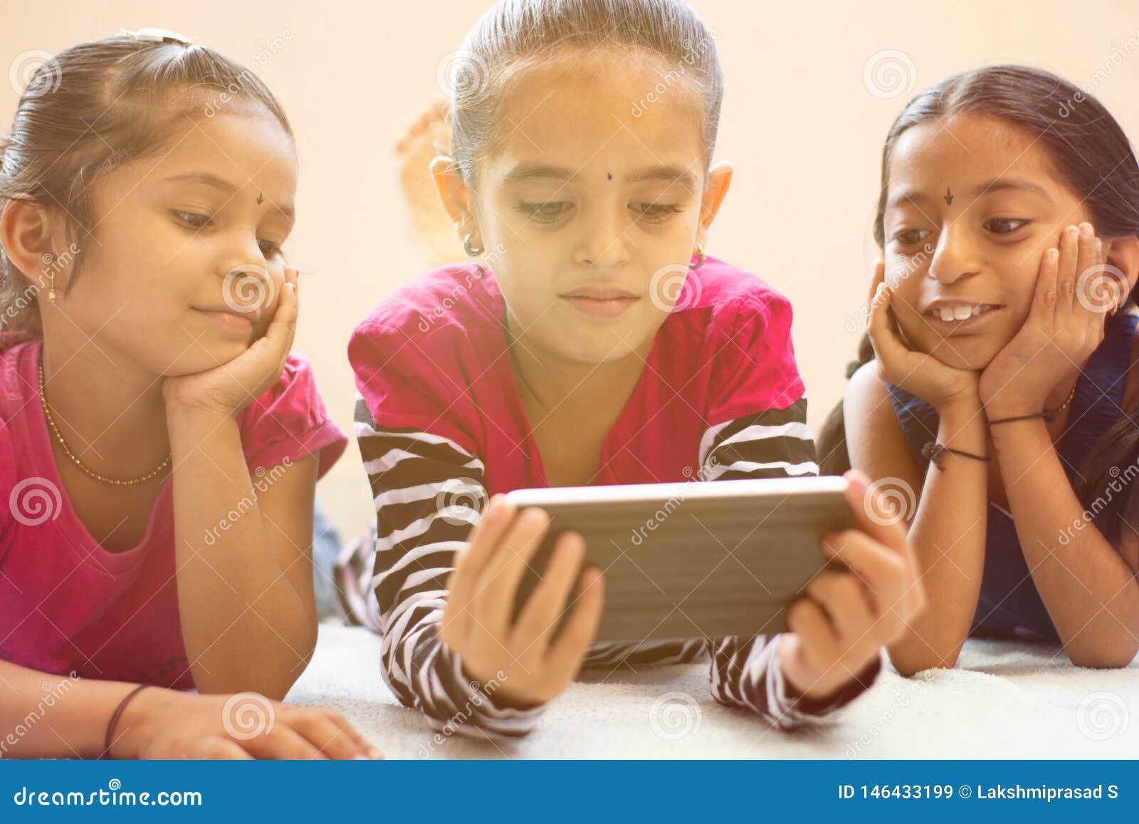 Tre bambini indiani svegli che guardano bambino che per mezzo dello smartphone con i fronti sorridente sul letto
