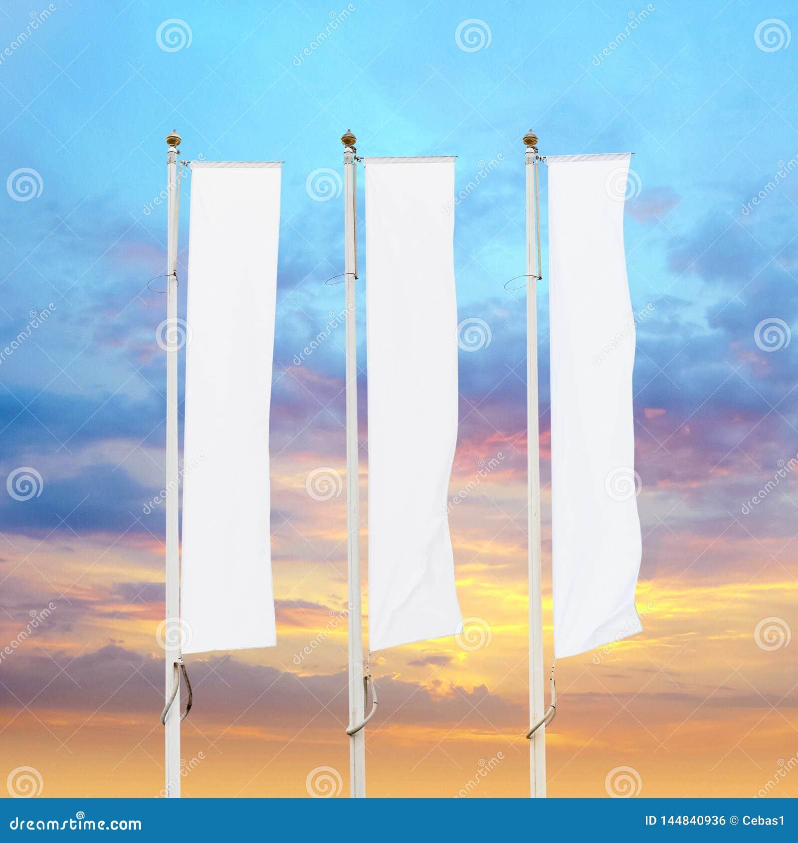 Tre bandiere corporative bianche in bianco con il fondo del cielo di tramonto