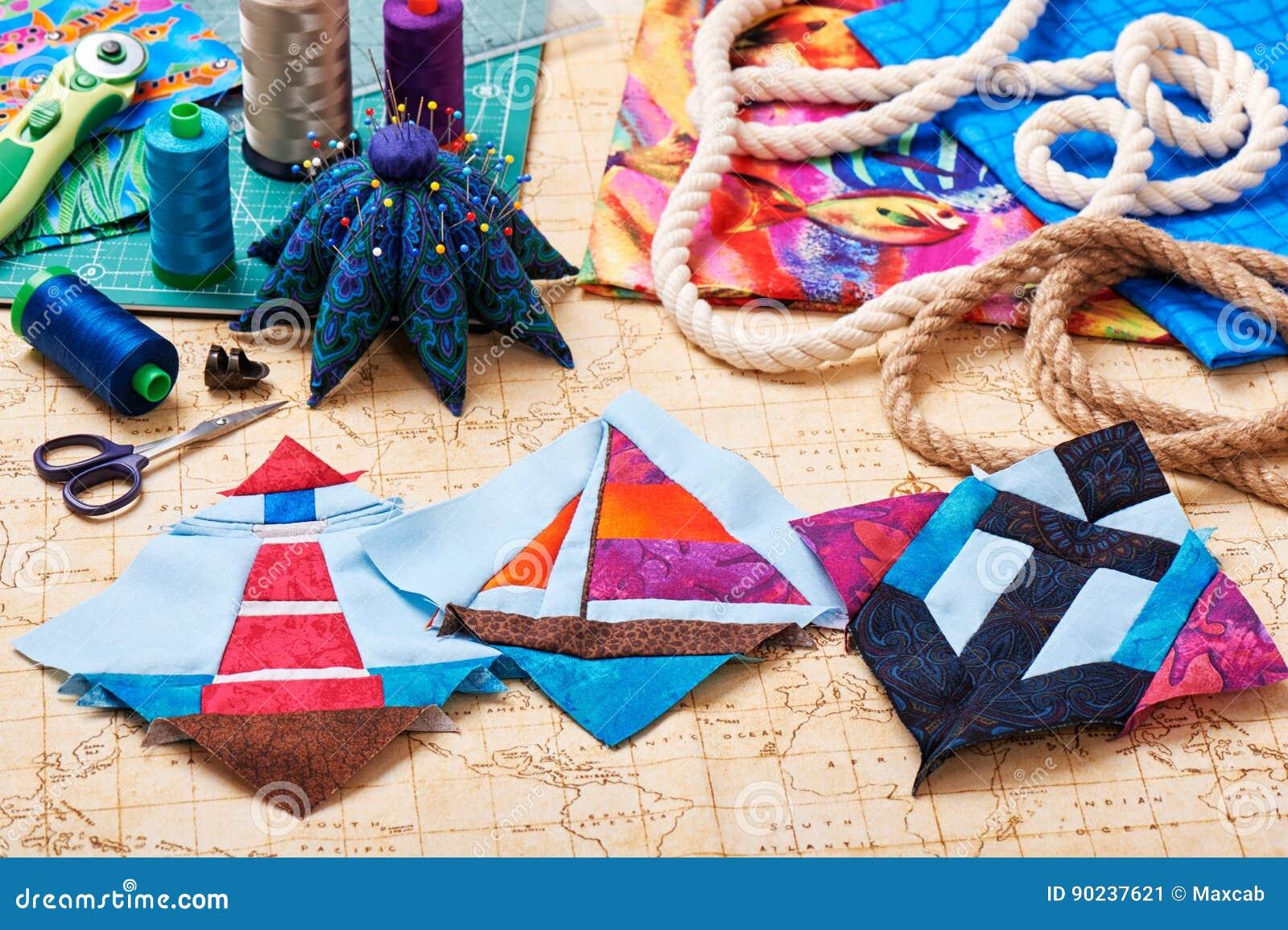 Tre blocchetti faro, yacht e ancora, tessuti, strumenti imbottenti ed accessori della rappezzatura