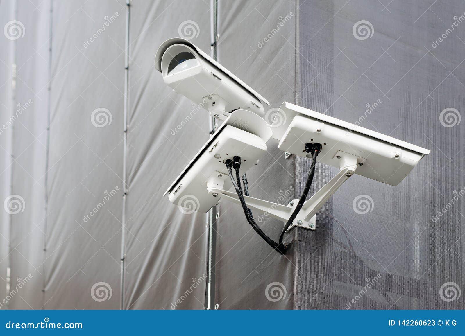 Tre CCTV-kameror på hörn av byggnad under återställande- eller förnyandedet fria Säkerhetskameror på väggen av konstruktionsbyggn