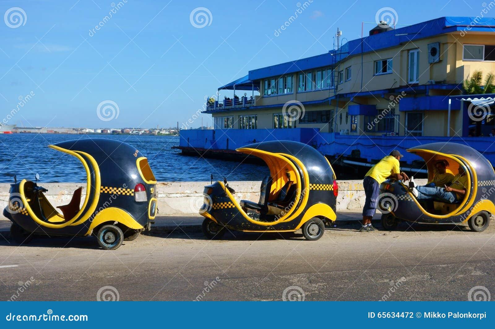 Tre Cocotaxis ed i loro driver nel porto di Avana