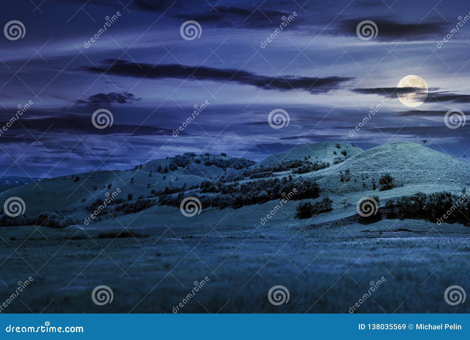 Tre colline nel paesaggio di estate alla notte
