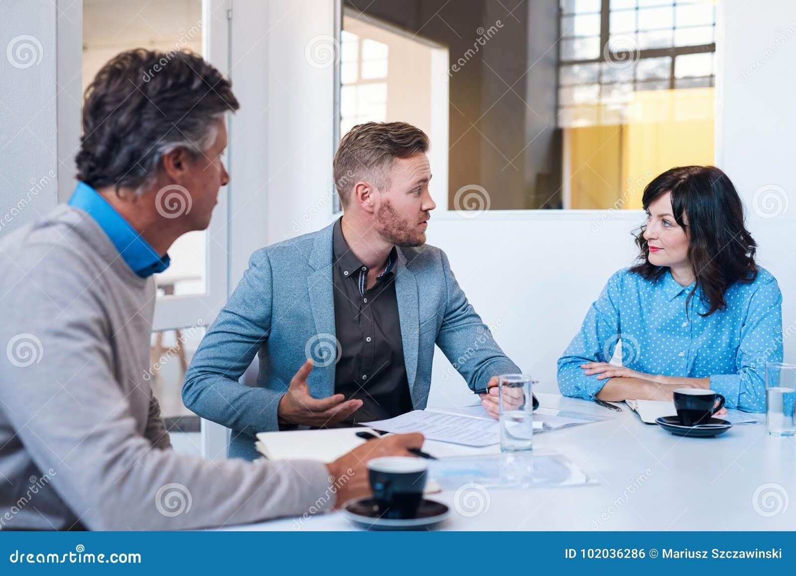 Tre coworkers som har ett strategimöte i ett modernt kontor