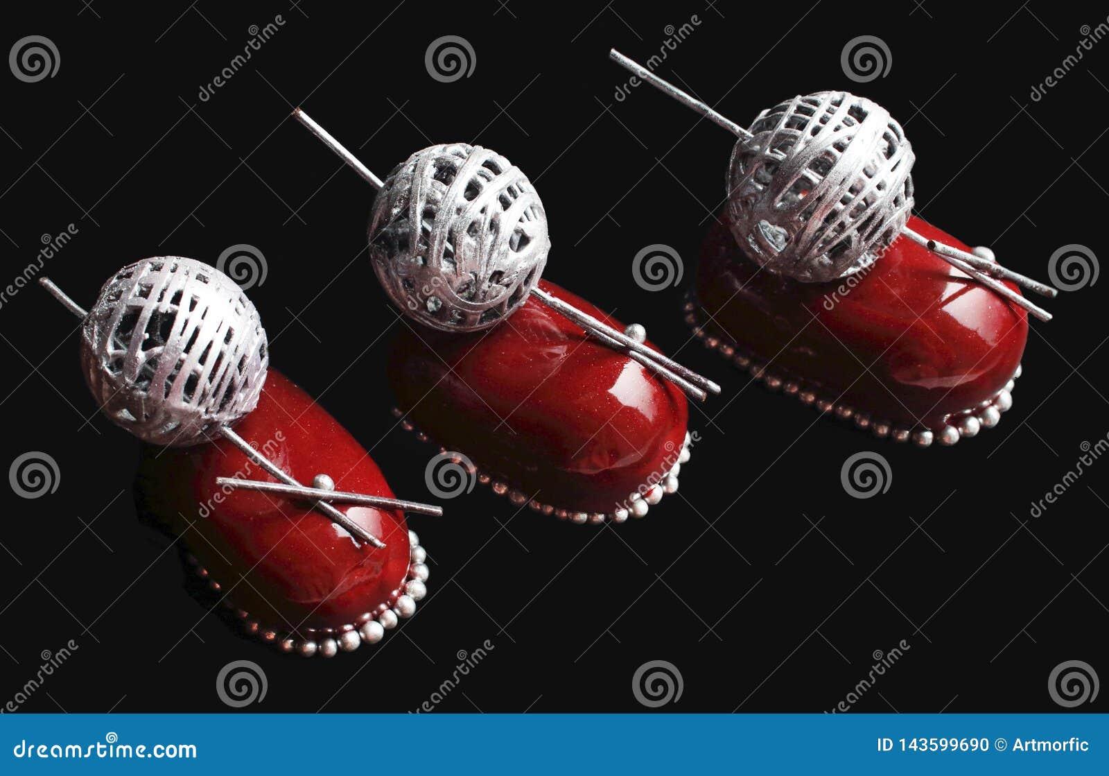 Tre dessert rossi della bacca del cioccolato con argentano la decorazione della palla della lana e spruzza