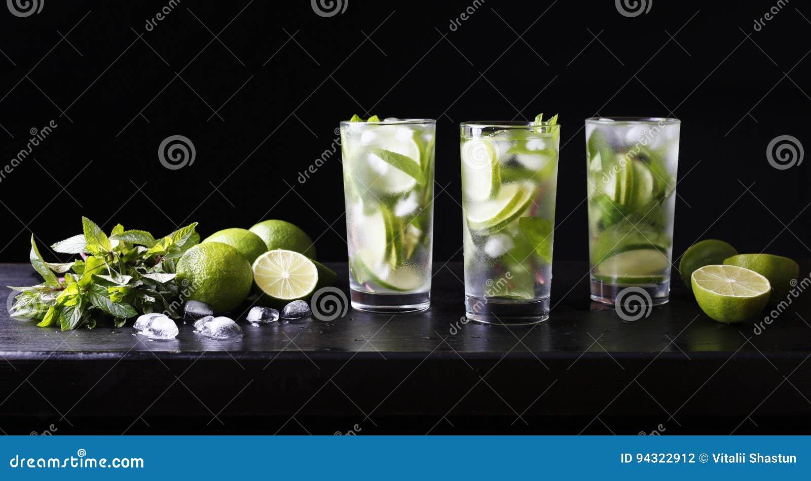 Tre exponeringsglas av coctailmojitolemonad på stången Particoctail Limefrukt, is och mintkaramell på tabellen Svart bakgrund