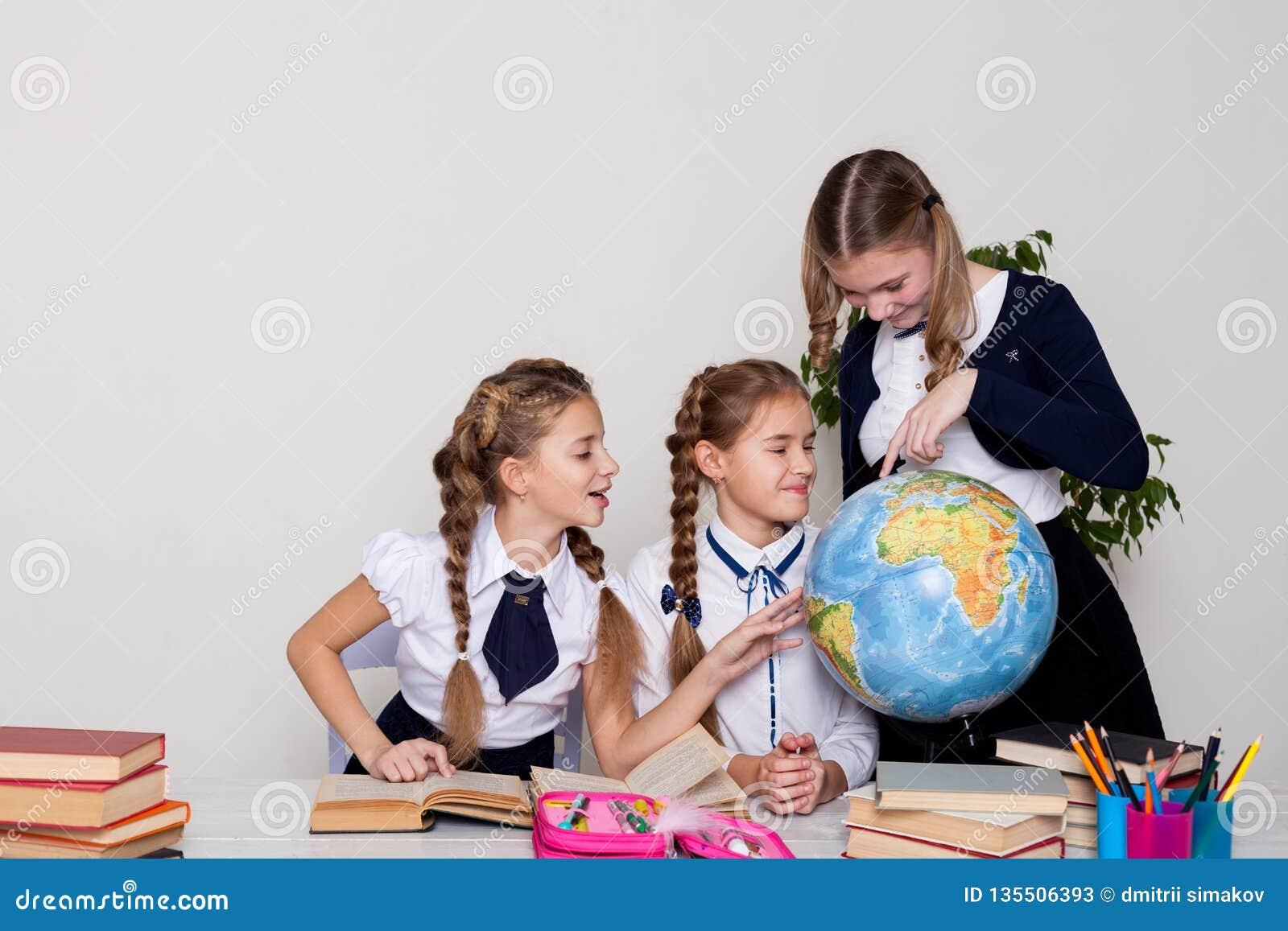 Tre flickaskolflickor på kursen av geografi med ett jordklot i skola