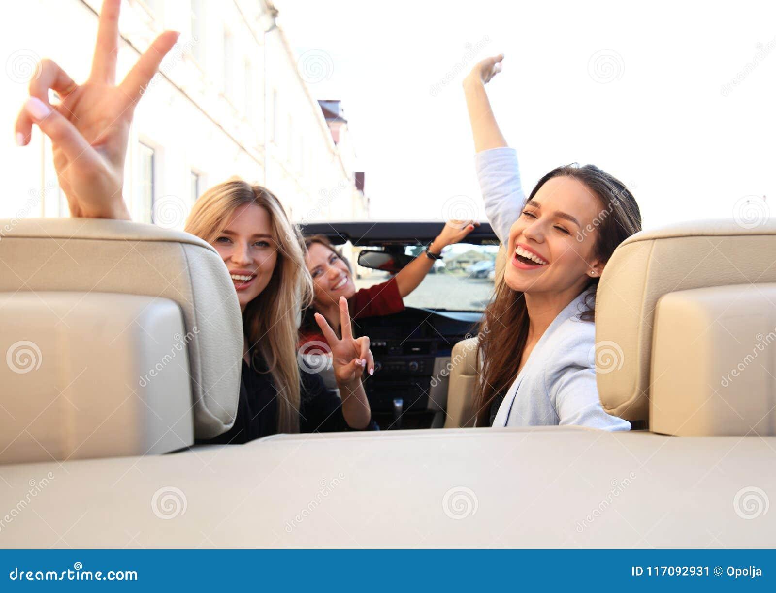 Tre flickor som kör i en konvertibel bil och har gyckel