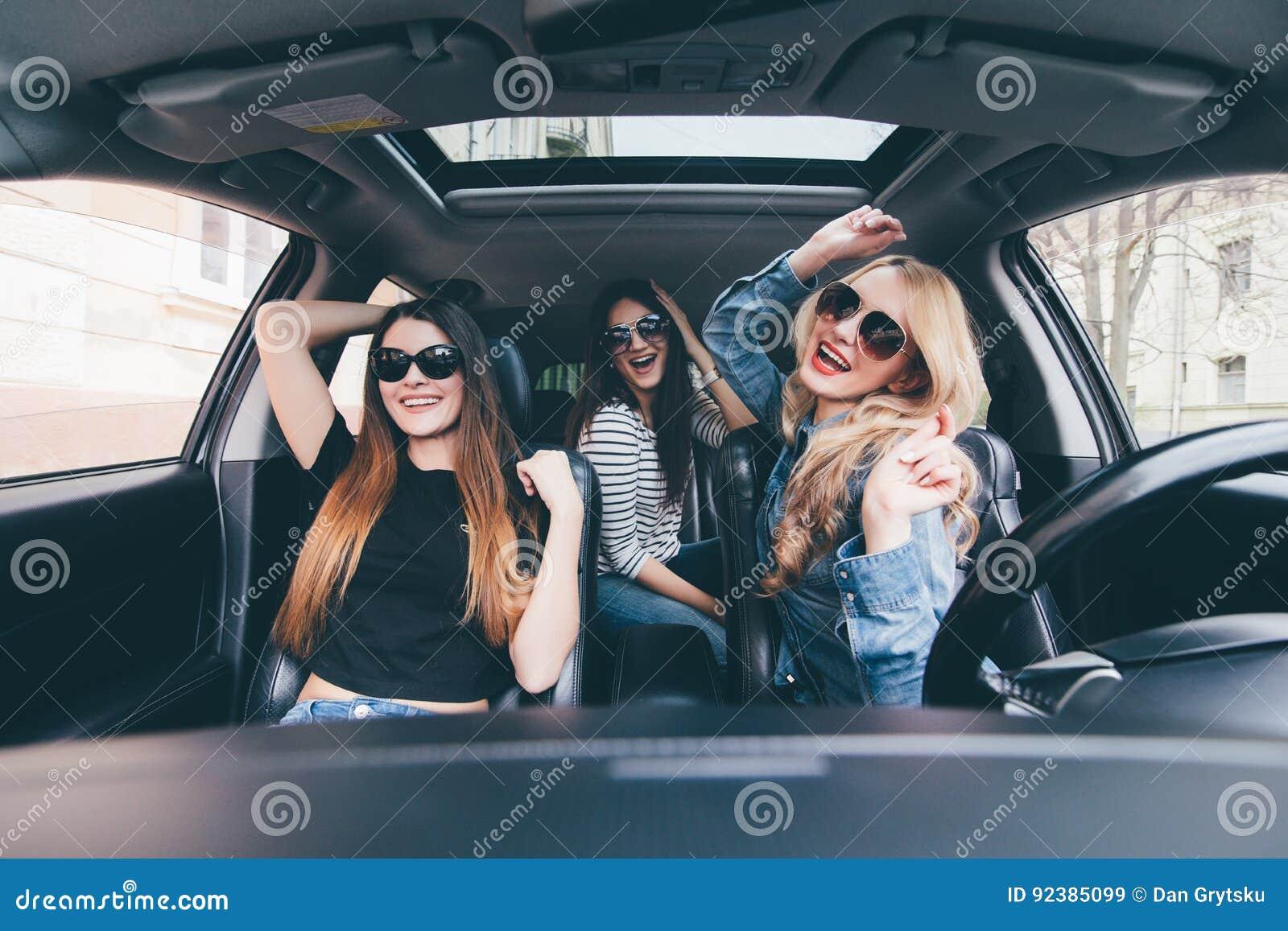 Tre flickor som kör i en konvertibel bil och har gyckel, lyssnar musik och dansar