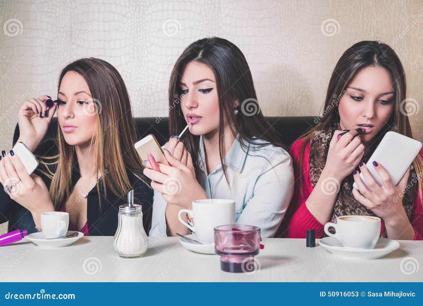 Tre flickor som sätter på makeup i ett kafé
