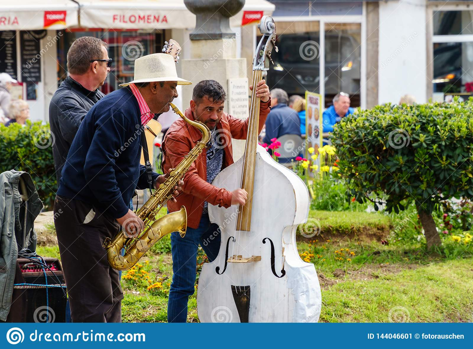 Tre gatamusiker som spelar för turister
