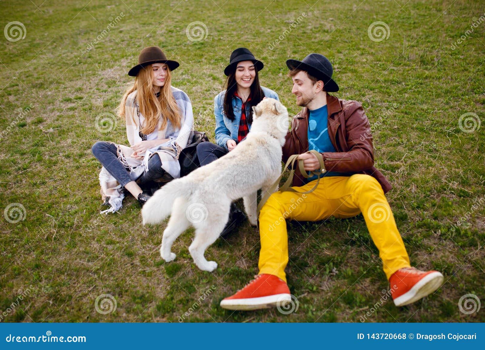 Tre giovani amici dei pantaloni a vita bassa di felicità che parlano sull erba verde e sul loro cane del husky