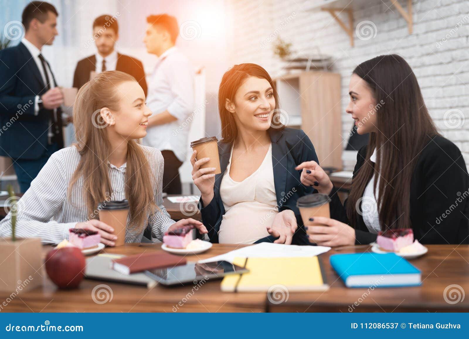 Tre giovani belle ragazze socializzano il caffè bevente e mangiare agglutina nell ufficio