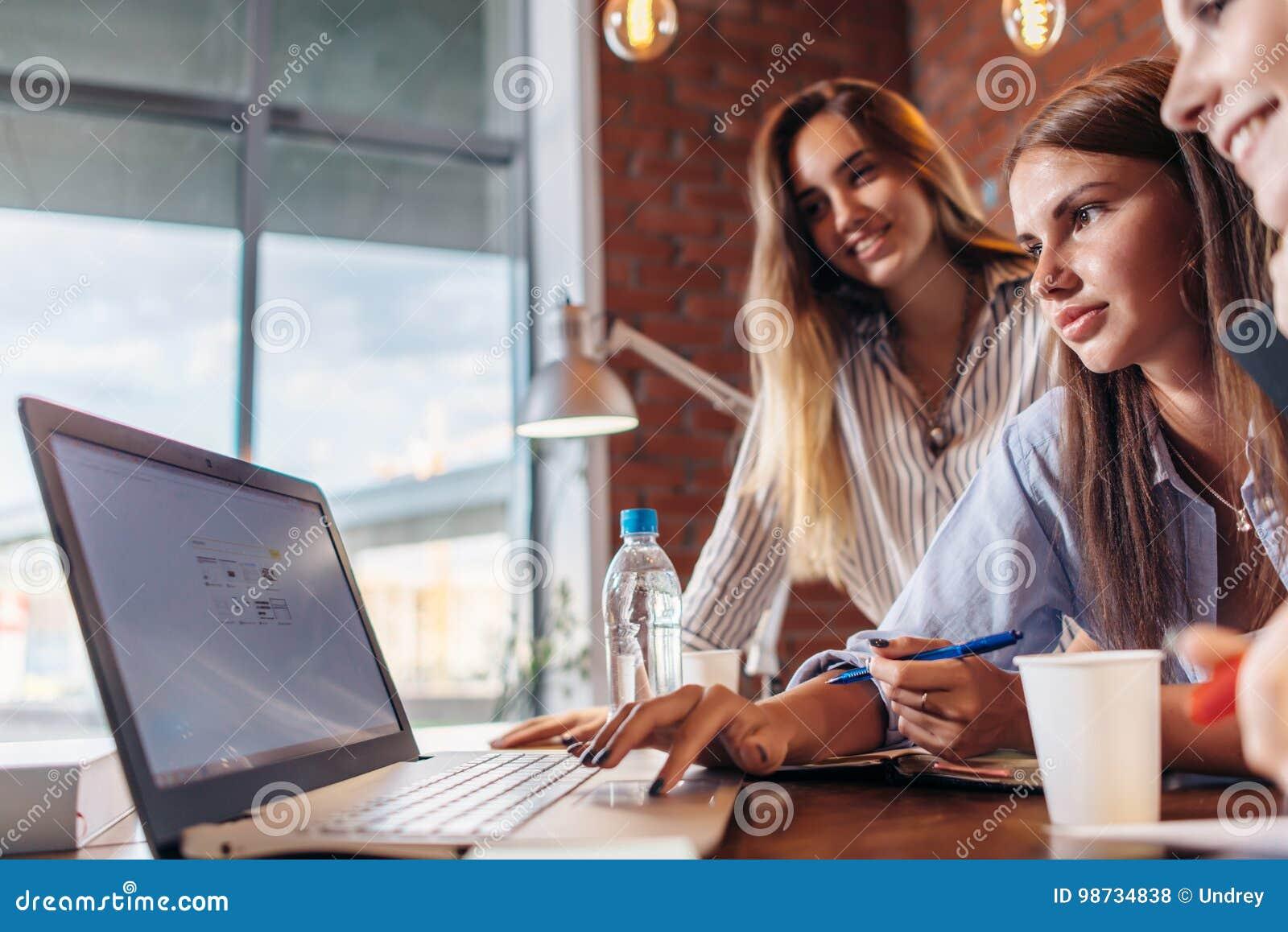 Tre gladlynta kvinnliga högskolestudenter som surfar internet genom att använda bärbara datorn som söker tillsammans informatione