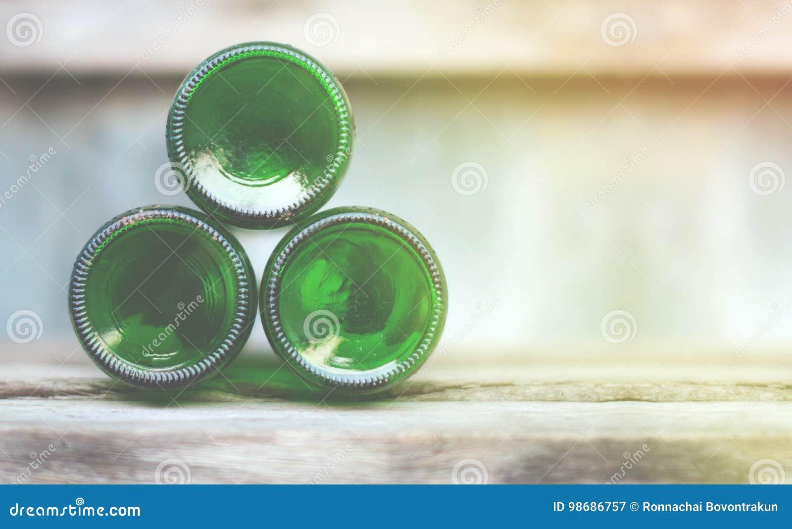 Tre glasflaskor, gröna bottnar ligger framåt på trä