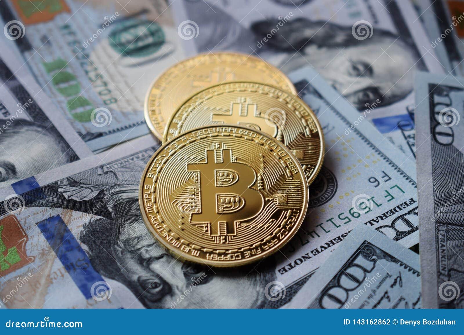 Tre guld- Bitcoin mynt på US dollar