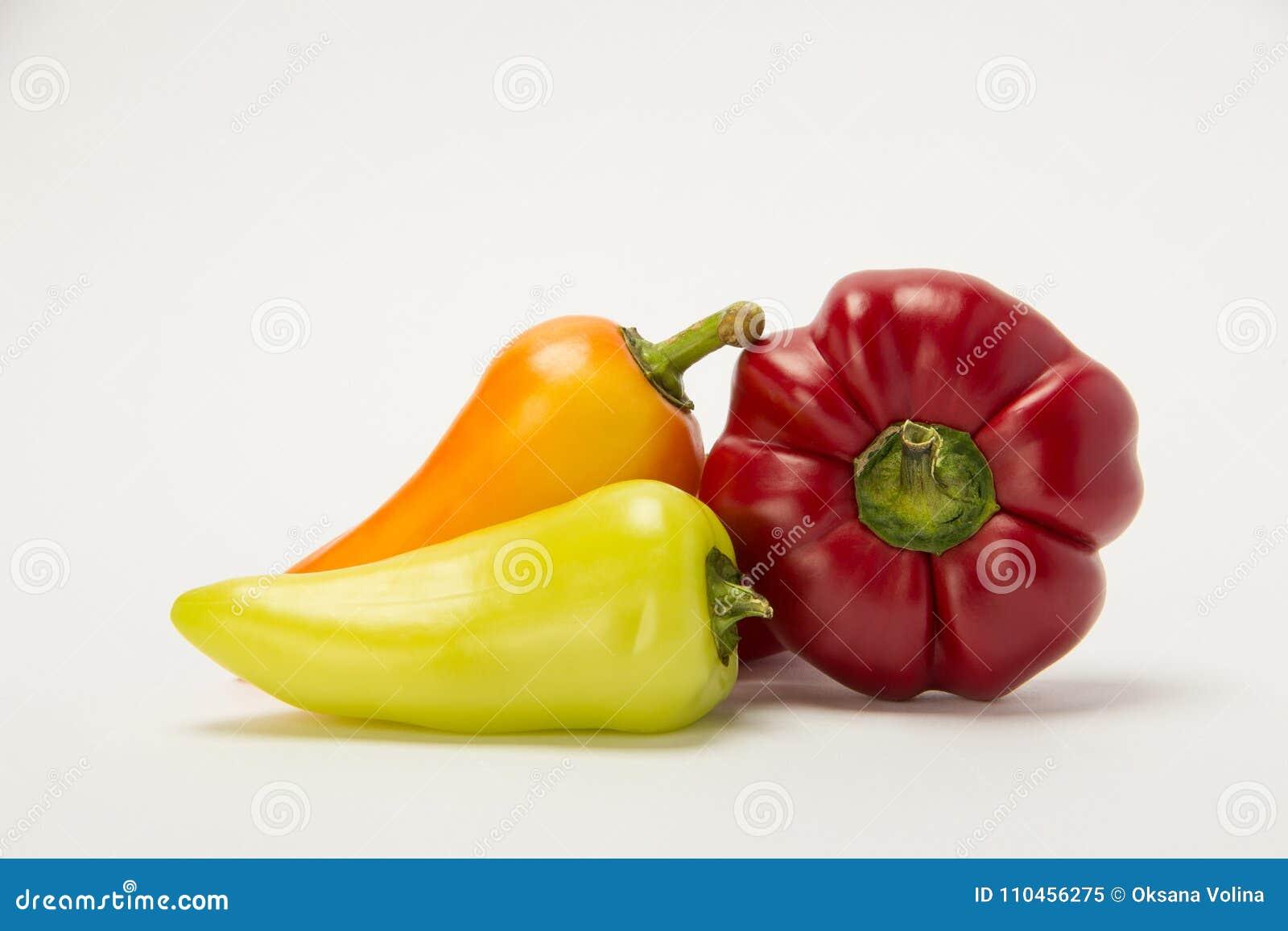 Tre härliga söta peppar på en vit bakgrund