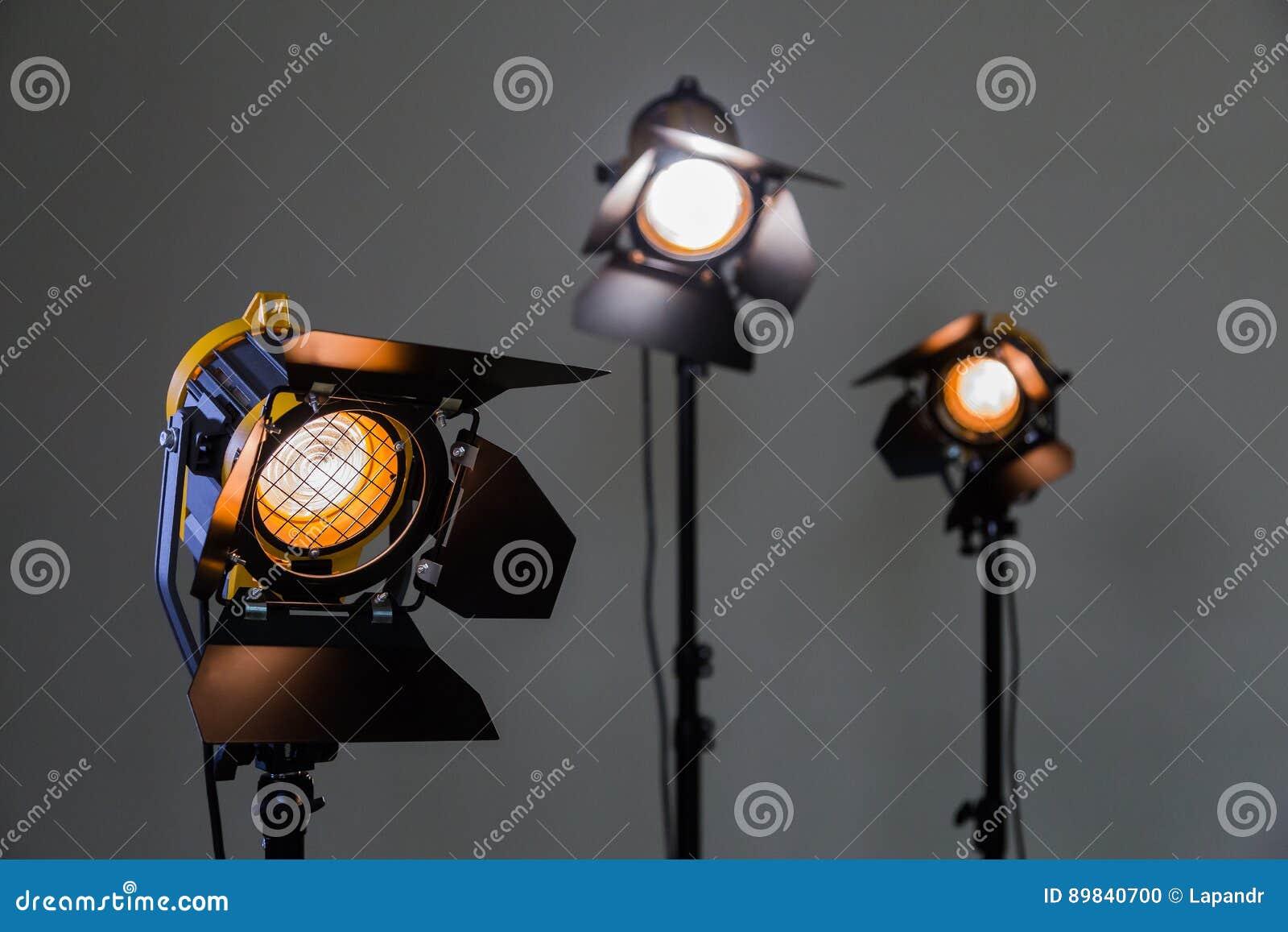 Tre halogenstrålkastare med Fresnel linser på en grå bakgrund Fotografera och filma i inre