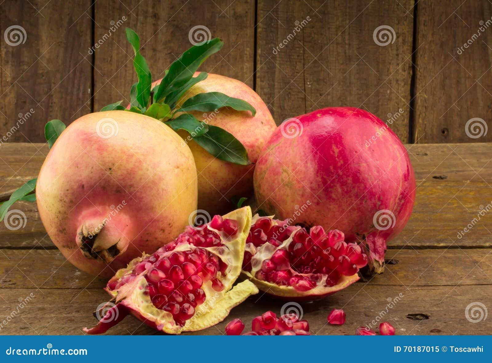 Tre hela granatäpplen, frö och stycken på lantlig wo