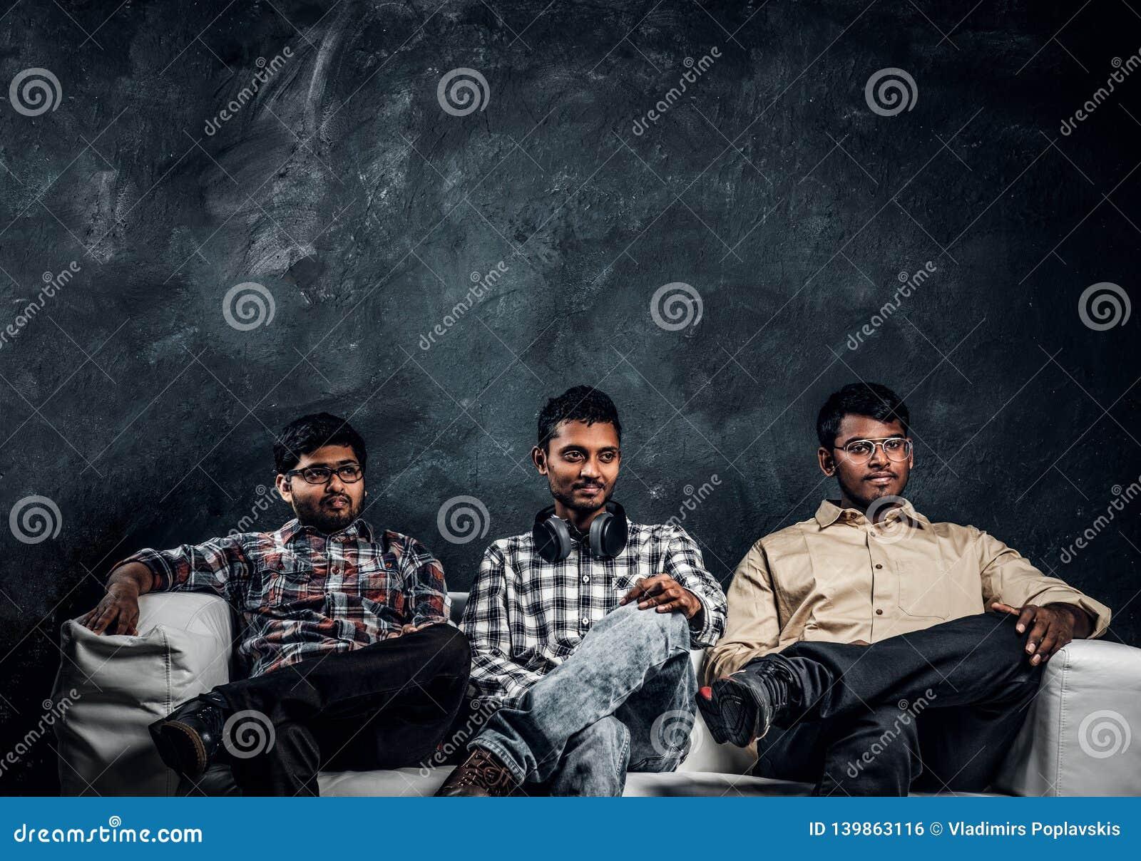Tre indiska studentvänner som bär tillfällig kläder som sitter på en soffa mot den mörka väggen