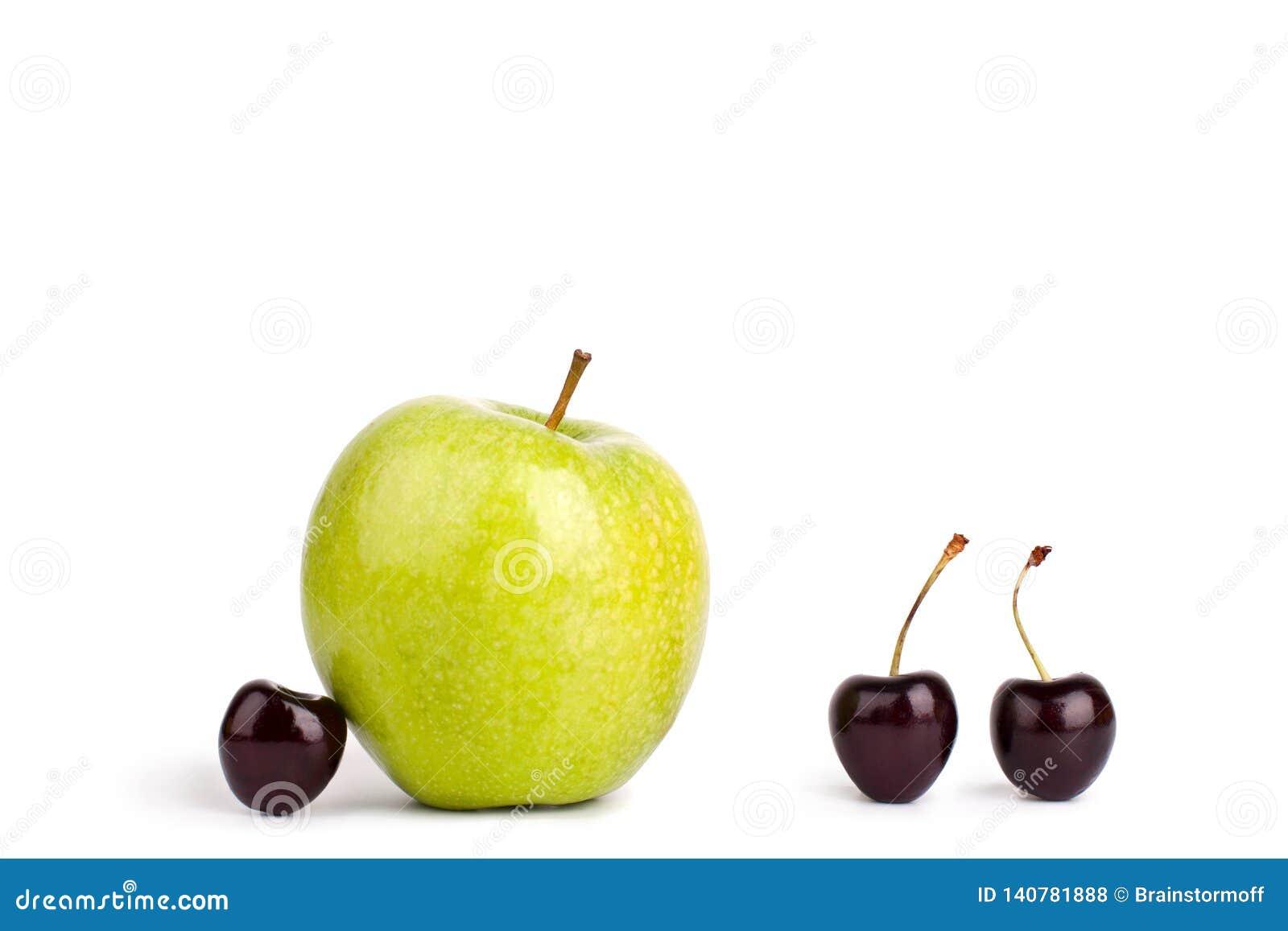 Tre körsbärsröda bär och ett stort grönt äpple på vit bakgrund isolerat slut upp makro